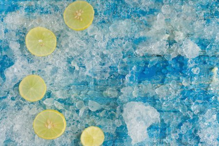 Crushed ice cubes and lemon slices on blue background