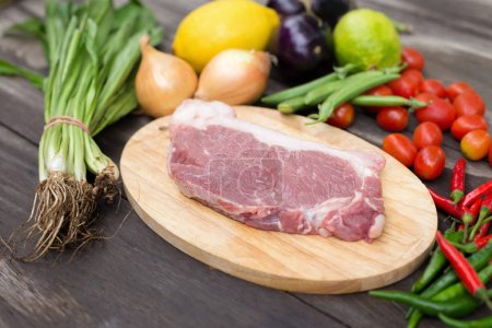 Uncooked meat with different ingredients on dark background