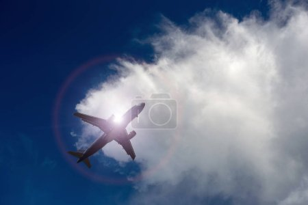 Airplane flying under blue sky and white cloud.