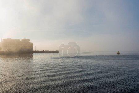 Photo pour Reflet du coucher du soleil sur la surface de l'eau du lac et jetée avec bâtiments - image libre de droit