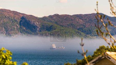 Photo pour Lac dans les montagnes, brouillard et bateau bateau sur l'eau - image libre de droit