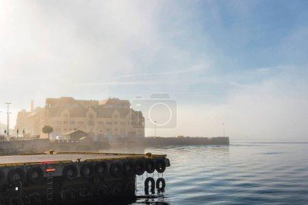 Photo pour Surface bleue de l'eau du lac et jetée avec bâtiments - image libre de droit