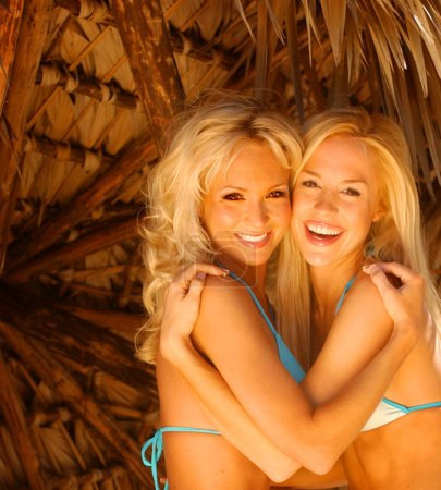 Photo for Celebrity models Mandy and Lauren posing with a smile - Blue string bikini - Ashford blonde curly hair - sexy blue bikini with tan palm leaf background copy space - Light makeup - Lots of  Cleavage - Tight abs - Tone Body - Tan skin adorable twins - Royalty Free Image