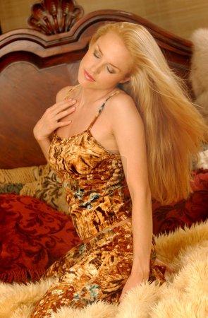 Photo pour Adorable Blonde aux cheveux longs posant dans un studio de chambre à coucher avec des oreillers de lit panneau de lit en bois brun et fourrure jaune bronzé comme fond d'espace de copie - Outfit est un simple feutre confortable et coloré vêtements de nuit doux flous - pose de catalogue de maquillage léger - image libre de droit