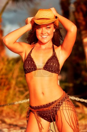 Photo for Cowboy hat and brown croquet tight weaved bikini - impressive abs on young fresh model with no makeup - nature look of a real beauty - Sunshine sun tan sun drenched sunny healthy attitude of a carefree babe - vogue pose by professional model - Royalty Free Image