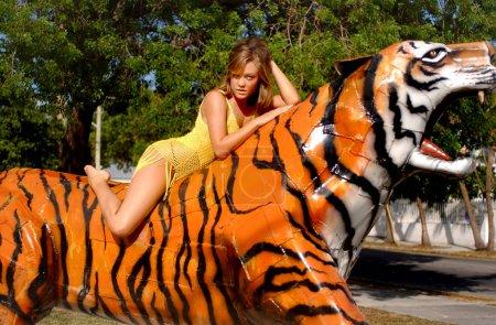 Photo pour Fille brune mince en forme athlétique dans la couverture pure jaune gisait sur le dessus d'un tigre orange du Bengale se détendre après avoir magasiné pour la tenue pendant les vacances dans le village de Key West Florida - pose amusante mais proactive - sourire ludique sur la jeune beauté - paysage - image libre de droit