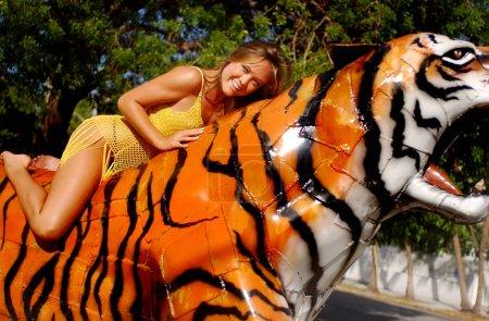 Photo pour Fille brune mince en forme athlétique dans la couverture pure jaune gisait sur le dessus d'un tigre orange du Bengale se détendre après avoir fait du shopping pour les tenues pendant les vacances dans le village de Key West Florida - pose amusante mais proactive - sourire ludique sur la jeune beauté - paysage - image libre de droit