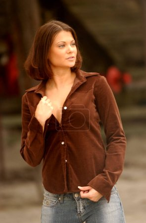 Photo pour Passive look - looking away from camera - Brown soft felt long sleeve cute top on large breasts and blue jeans  Professional fashion model  - Tan tone clear skin - pretty face - image libre de droit