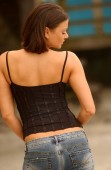 Passive look - looking away from camera - black shoulder strap  cute top on large breasts and blue jeans  - Professional fashion model  - Tan tone clear skin bare arms