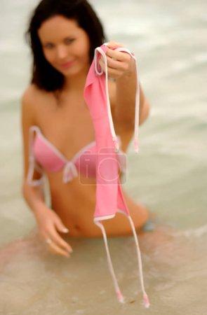Photo pour Pink bikini bottoms off sea water waves happy girl smile pretty brunette plays in Atlantic Ocean - image libre de droit