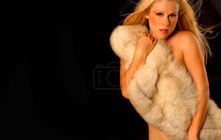 Photo pour Playboy model Deana Durbin poses in tan fur stole on black background for wallpaper isolated - image libre de droit