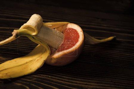 Photo pour Banane avec pelure jaune au pamplemousse rouge sur fond en bois, le sexe et les rapports sexuels, l'amour fruit, vitamine et régimes amaigrissants, saine alimentation, pénis et vagin - image libre de droit