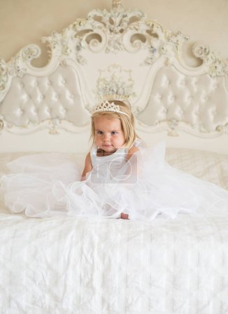So good to be the queen. Little child with long blond hair. Little girl wear tiara crown and hairstyle. Hair accessory. Small blond child sit on bed. Beautiful hairstyles for baby girls. Cute sweetie