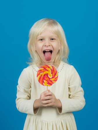 Get lost in the hypnotic swirl. Happy candy girl. Little girl hold lollipop on stick. Little child with sweet lollipop. Happy childhood food