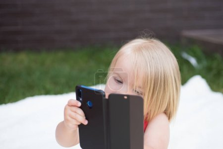 Cell phone dependency. Small child make phone call. Small girl use mobile phone. Girl child with blond hair talk on cell phone. New technology for children. The joy of best hair