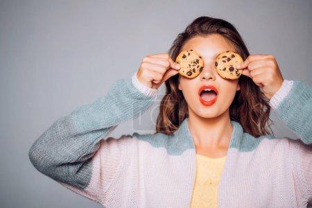Photo pour Les cookies sont tellement amusants et simples. Jolie fille couvrant des yeux avec des biscuits. Fille mignonne ayant l'amusement avec des biscuits. Recette de biscuit de chocolat de modèle de boulangerie. Magasin de boulangerie. Suivre une recette de cuisine. - image libre de droit