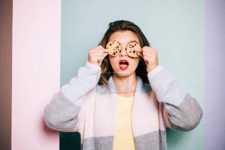 Photo pour Suivant une recette de cuisine. Jolie fille couvrant des yeux avec des biscuits. Fille mignonne ayant l'amusement avec des biscuits. Recette de biscuit de chocolat de modèle de boulangerie. Magasin de boulangerie. Obtenir des biscuits parfaitement épais. - image libre de droit