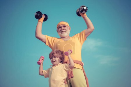 Photo for Happy little boy with grandfather is doing exercises with dumbbells. Father and son spotting. Cute kid and senior man exercising with dumbbells - Royalty Free Image