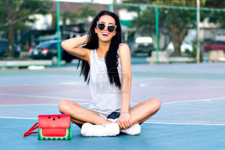 Photo pour Femme brune excitée assise avec les jambes croisées au terrain de basket et jouant avec ses cheveux. Portrait extérieur de fille souriante dans des lunettes de soleil posant sur le sol près du sac avec la conception de pastèque . - image libre de droit