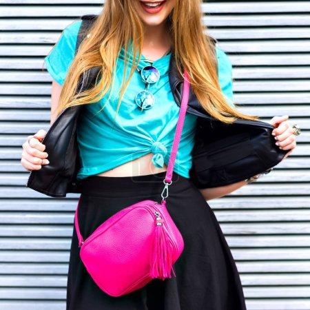 Photo pour Jeune femme avec le sac rose croix posant sur la rue - image libre de droit