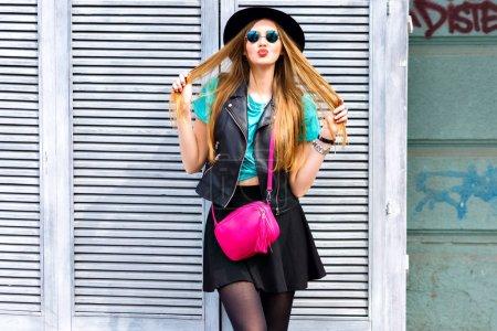 Photo pour Belle jeune femme avec le sac rose croix posant sur rue baiser gonflant - image libre de droit