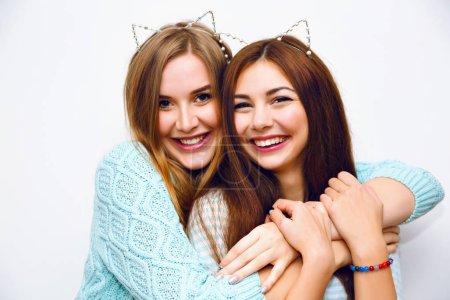 Photo pour Gros plan mode style de vie portrait de deux jeunes filles hipster meilleurs amis dans les oreilles bandeaux posant en studio - image libre de droit