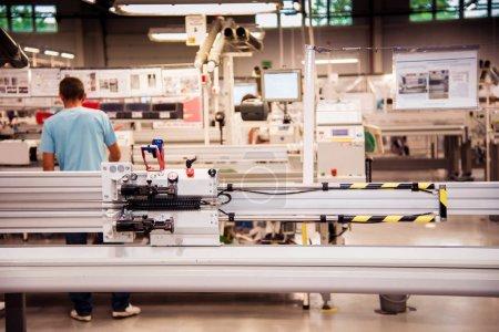 Photo pour Paysage industriel avec un travailleur derrière une machine outil, qui fait partie du câblage pour les voitures dans une usine moderne à un atelier de production - image libre de droit