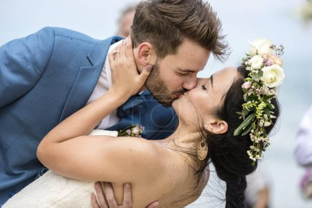close-up shot of cheerful newlyweds kissing at beach wedding ceremony
