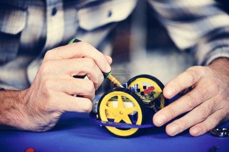 Closeup of hands working on robot wheels