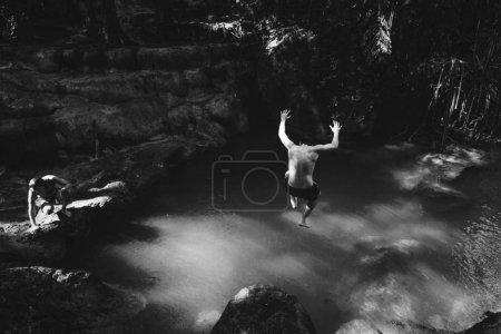 Man jumping into a natural pond