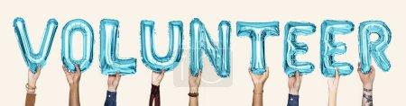 Blue alphabet balloons forming the word volunteer