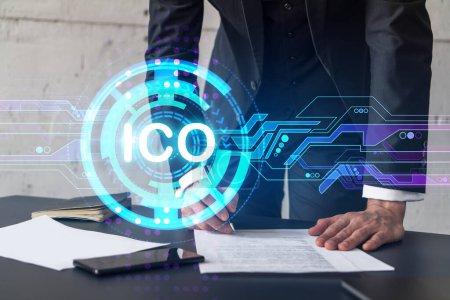 Geschäftsmann im Anzug signiert weißen Papper. Doppelbelichtung mit ICO-Symbol-Hologramm. Mann unterschreibt Vertrag. Blockchain-Marktanalyse und Anlagekonzept.