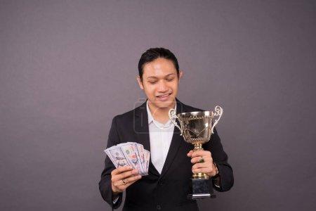 Photo pour Un jeune homme d'affaires tenant argent et trophée d'or.Réalisation réussie . - image libre de droit