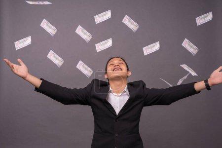 Photo pour Un jeune homme d'affaires célébrant sa réussite et jetant beaucoup d'argent à l'air . - image libre de droit