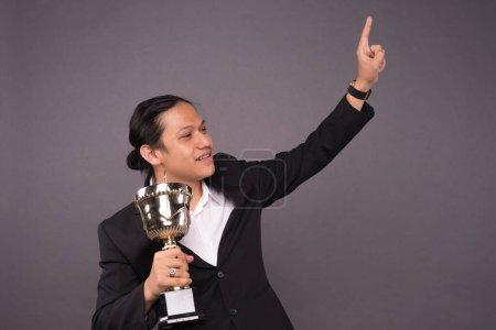 Photo pour Un jeune homme d'affaires tenant un trophée d'or et célébrant son archivage . - image libre de droit