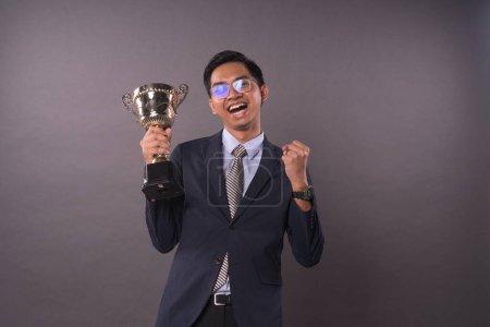 Photo pour Heureux jeune homme intrepreneur ou homme d'affaires tenant son trophée d'or et célébrant sa victoire.Studio shot . - image libre de droit