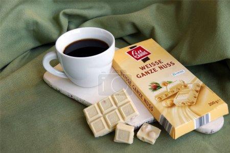 Photo pour KHARKOV, UKRAINE - 10 FÉVRIER 2020 : Fin Carre, Weisse Ganze Nuss Barre de chocolat blanc allemande aux noisettes entières et une tasse blanche avec café frais. Petit déjeuner sur un bureau en bois blanc. - image libre de droit