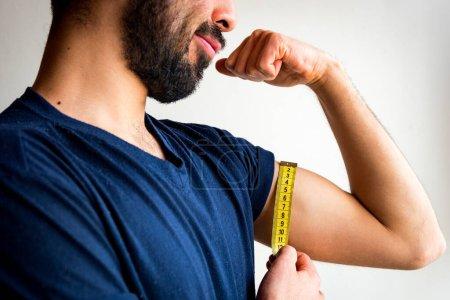 Photo pour Homme mince porté mesurant des biceps, muscles de son bras gauche avec un ruban à mesurer jaune. Il est triste, frustré, déçu. T-shirt bleu. Fond blanc. - image libre de droit