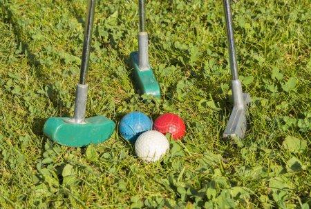 Photo pour Balles de golf et clubs de golf sur herbe verte - image libre de droit
