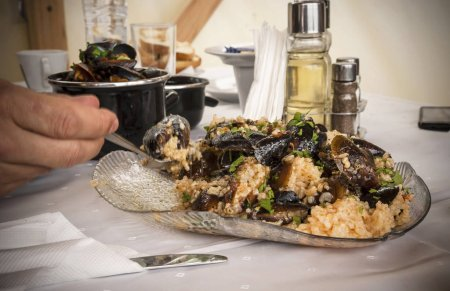 Photo for Lunch time. Eating mussels with rice. - Royalty Free Image