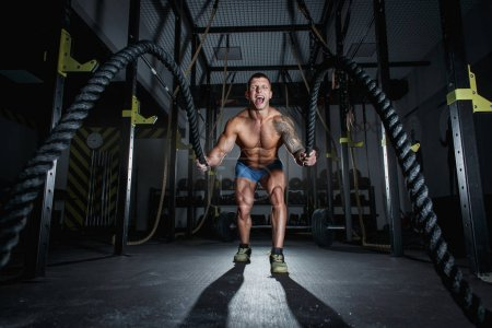 Photo for Athletic pumped man bodybuilder is engaged with ropes in hall of crossfit - Royalty Free Image