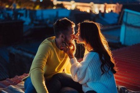 Photo pour Le couple aimant est assis sur le toit de la maison. Au loin, les lumières de la ville nocturne . - image libre de droit