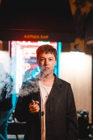 Photo pour Jeune homme posant sur la caméra, debout près du bar - image libre de droit