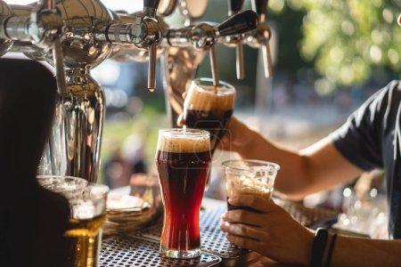 Photo pour Barman verse de la bière noire dans un verre au bar close-up - image libre de droit