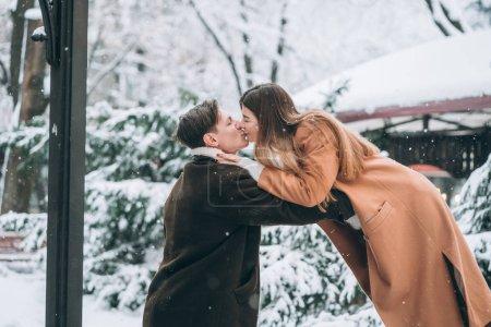 Photo pour Jeune homme et belle fille baiser dans un parc enneigé à la caméra - image libre de droit