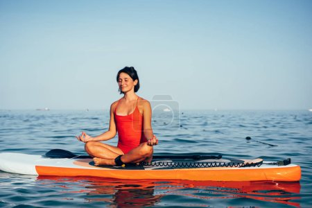 Young woman doing yoga on sup board with paddle. M...