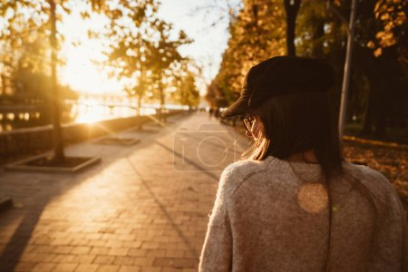 Photo for Attractive, young brunette with long hair walking autumn park. View from behind. - Royalty Free Image