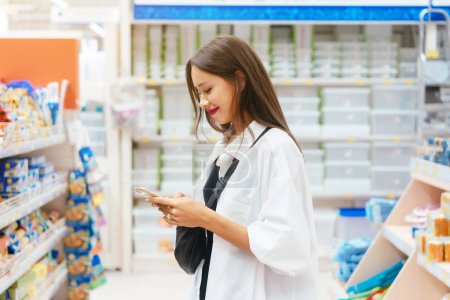 Photo for Close up view girl buy products using smartphone in store. Young woman shopping in supermarket blur background - Royalty Free Image