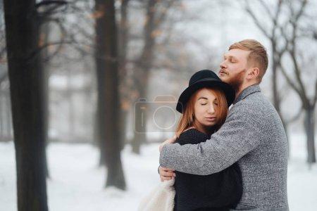 Photo pour Le gars et la fille se reposent dans la forêt d'hiver. Jeune couple marchant dans un parc d'hiver . - image libre de droit