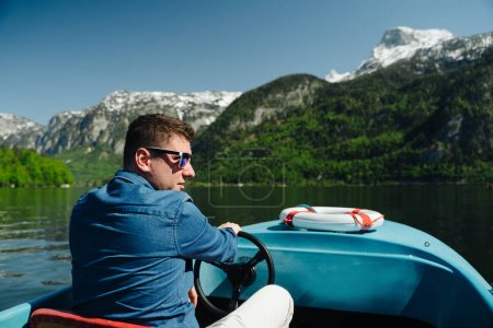 Photo pour Beau jeune homme contrôle un bateau à moteur sur un lac de montagne, les montagnes en arrière-plan - image libre de droit